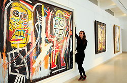 © Licensed to London News Pictures 10/04/2013.A Christie's employee straightens the Jean-Michel Basquiat painting 'Dustheads' (estimated between $25 -$35 million) that, along with Roy Lichenstein's 'Woman with Flowered Hat' (estimated at $30 million), (centre), and Francis Bacon's 'Study for Portrait' (estimated between $18 - $25 million), (far right), are some of the major works on display at Christie's in central London, and due to go on auction on the 15th May in New York. .London, UK.Photo credit: Anna Branthwaite
