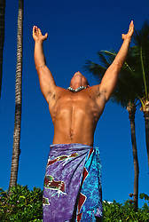 hairless muscular man in a sarong lifting his arms towards the sky in Hawaii