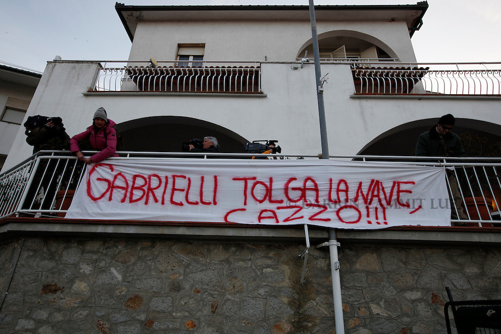 """Residents hang a bang reading """"Gabrielli get rid of the fucking ship"""" before a meeting for locals to discuss the situation following the shipwreck of the Costa Concordia off the west coast of Italy at Giglio island January 30, 2012. The banner refers to the Civil Protection agency chief Franco Gabrielli, who is in charge of the salvage operation, who said removing the massive wreck from its position outside the port could take up to a year...REUTERS/Darrin Zammit Lupi (ITALY)"""