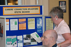 A full time carer looks at leaflets and information with her disabled husband Bradford