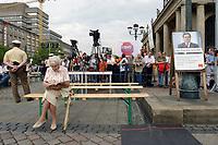 05 AUG 2002, HANNOVER/GERMANY:<br /> Eine alte Frau wartet noch allein auf einer Bank neben einem Plakat auf dem Gerhard Schroeder zu sehen ist, auf den Beginn der SPD Kundgebung zum Wahlkampfauftakt, Opernplatz<br /> IMAGE: 20020805-01-010<br /> KEYWORDS: Rentner, Rentnerin, Wahlkampfplakat