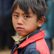 A  young boy at the Lung Khau Nhin Market. Vietnam. Lung Khau Nhin Market is rural tribal market hiding itself amongst the mountains and forests of the far north Vietnam about 10 km from the border with China. The market plays an important role for the local ethnic people, Flower Hmong, Black Zao, Zay, and very small ethnic groups  Pa Zi, Tou Zi, Tou Lao. Tourist trips to the market run from Sapa and Lao Cai every week. Lung Khau Nhin Market, Vietnam.15th March 2012. Photo Tim Clayton