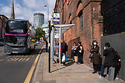 As numbers of Covid-19 cases in Birmingham have dramatically risen in the past week, increased lockdown measures have been announced for Birmingham and other areas of the West Midlands, people wearing face masks waiting at a bus stop a s abus to Solihull passes just outside the shopping district in the city centre on 12th September 2020 in Birmingham, United Kingdom. With the rule of six also being implemented the Birmingham area has now be escalated to an area of national intervention, with a ban on people socialising with people outside their own household, unless they are from the same support bubble.