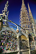 Watts Towers, Los Angeles, California. Designed by Simon Rodia 1921-1955. Untrained as an architect, engineer, or builder, Simon Rodia created a complex of towers that rose over one hundred feet tall. Composed of structural steel rods and circular hoops connected by spokes, the towers incorporate a sparkling mosaic of found materials including pottery, seashells, and glass. Rodia's house, destroyed by fire in 1957, resided within the complex..Declared hazardous by the city of Los Angeles, the towers were threatened with demolition until an engineer's stress test proved them structurally sound. They have since been designated a cultural monument. USA.