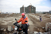 A man rides a motorbike through a new apartment development in Kunshan, Jiangsu Province, China on 25 October, 2011. As China's central government shows no intention to loosen its policy restrictions on the housing market despite 4 consecutive  months of price drops,  local governments must find a way to repay the 10.7 trillion yuan ($1.7 trillion) in debt as their land sale revenue dropped 13 percent from the previous year and with no end in sight.