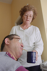 Carer holding cup of tea while man with Cerebral Palsy drinks it through straw,