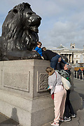A tourist is pushed up on to the plinth of one of four lions in Trafalgar Square, on 8th October 2018, in London, England. The lions are by Sir Edwin Henry Landseer RA, an English painter well known for his paintings of animals—particularly horses, dogs and stags. The best known of Landseers works, however, are these lions in Trafalgar Square.