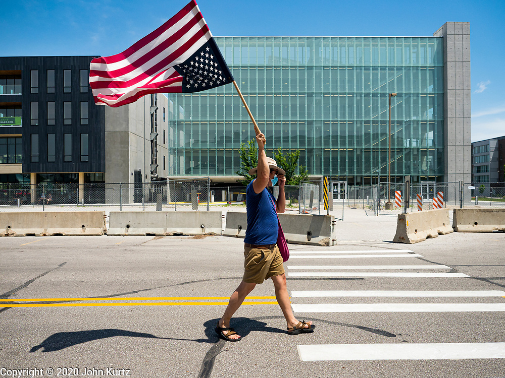 06 JUNE 2020 - DES MOINES, IOWA: A Black Lives Matter supporter carries an upside down American flag while he marches in front of the Des Moines City Hall. In nautical terms, an upside down flag is a signal of a ship in distress. More than 1,000 protesters marched through downtown Des Moines to the state capitol to demand an end to police violence against Black people. The march was organized by Black Lives Matter and honored George Floyd, the unarmed Black man killed by Minneapolis police on 25 May 2020.        PHOTO BY JACK KURTZ