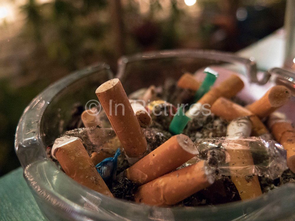 Overflowing ashtray or cigarette butts in a bar in London, UK. Smoking remains the top health concern in the UK.