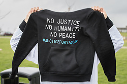"""© Licensed to London News Pictures. 06/01/2017. Huddersfield, UK. A man holds up a hoodie with """" No justice no humanity no peace #justiceforyassar"""" at the funeral of Yassar Yaqub at Hey Lane Cemmetary in Huddersfield, West Yorkshire. Yaqub, 28, from Huddersfield, was shot dead in a car stopped near junction 24 of the M62 as part of a planned police operation. Photo credit: Joel Goodman/LNP"""