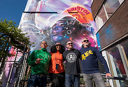 "© Licensed to London News Pictures; 02/04/2021; Bristol, UK. Poet LAWRENCE HOO, JEN REID, artist MR CENZ, and Jen's husband ALASDAIR DOGGART in front of ""United Souls United Goals"", an artwork by artist Mr Cenz, of a giant mural of Jen Reid, the woman who stood on the plinth of the statue of Edward Colston after it was torn down at a Black Lives Matter protest in Bristol in 2020 and of whom a statue was made and temporarily placed on the plinth. The mural is on the wall by The Canteen on Stokes Croft directly opposite Banksy's Mild Mild West mural, and replaces an earlier mural of Breakdancing Jesus. The mural is launched by The Bristol Eighteen and has the welcoming message ""Rise up Bristol, stand tall... Bristol's a city for all"" by poet Lawrence Hoo with Bristol's own street artist Inkie lending a hand to convey Lawrence Hoo's open-arms message of togetherness. The piece has been created to commemorate the Black Lives Matter protest in Bristol on June 7th 2020 and promote the ongoing global anti-racism movement. The Bristol Eighteen was formed, in the wake of the removal of Edward Colston's statue, to create a vehicle to raise funds for anti-racist educational organisations. Photo credit: Simon Chapman/LNP."