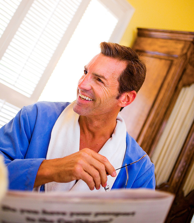 Male model in bathrobe relaxes in luxurious Fisher Island Club bedroom