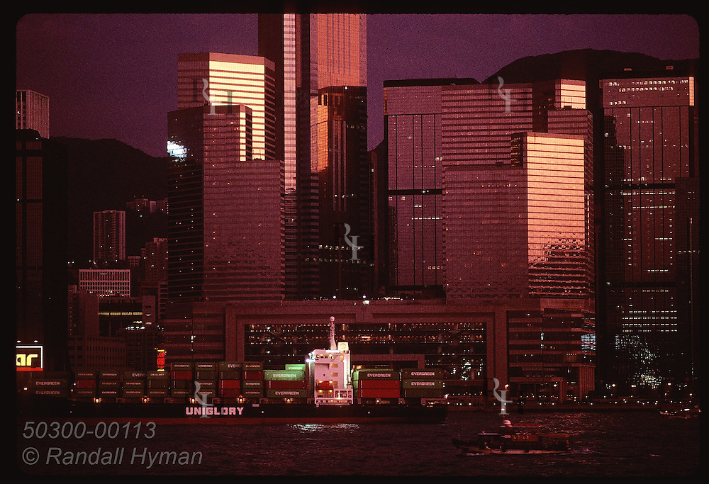Glass skyscrapers dwarf cargo ship moored in Hong Kong harbor at sunset;(h) view from Kowloon. Hong Kong