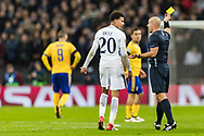 Referee, Szymon Marciniak gives Tottenham Hotspur midfielder Dele Alli a yellow card during the Champions League match between Tottenham Hotspur and Juventus FC at Wembley Stadium, London, England on 7 March 2018. Picture by Toyin Oshodi.