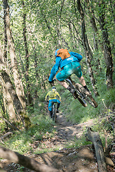 Biker jumping in mid-air while riding bike and following other biker on dirt path