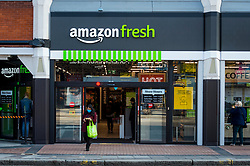 "© Licensed to London News Pictures. 07/03/2021. LONDON, UK.  A customer departs the new 2,500 sq ft Amazon Fresh store in Ealing, west London on its first weekend of opening. It is the first ""just walk out"" grocery store in the UK and the first outside the USA.  As a ""contactless"" shop, it is available to anyone signed up to Amazon and with the app on their smartphone.  In-store cameras and artificial intelligence monitor customers picking up items who simply walk out and billing takes place later automatically.  Photo credit: Stephen Chung/LNP"
