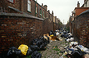 Poor terraced housing and alleyway in Liverpool with black refuse bags left against poor housing brick walls. Surrounded by black bin-bags during the Merseyside dustmen's' strike of 1991, we see a cobbled alley of 'back to back' houses in a poor area, South of the city centre, and home to deprived families. The industrial action against the local authority was a health problem for Liverpool during the summer of '91 when streets filled with rubbish. Vermin like rats ran around and public city parks filled with every kind of refuse and garbage. Few of these back-to-backs exist after being cleared to allow construction of high-rise tower-blocks and flats.