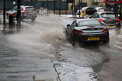 Constant rain on Bank Holiday Sunday leaves large puddles at Old Street Roundabout, with vehicles splashing water onto the pavement where pedestrians risk a soaking. London, August 26 2018.