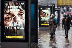 Edinburgh, Scotland, UK. 27 January 2020. Members of the public walk past new Government Covid-19 health warning display posters on Princes street in Edinburgh today. Iain Masterton/Alamy Live News