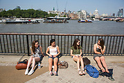 Four girls sitting in the sun beside the River Thames on the Southbank, London, UK. This is a popular place for Londoners to come and hang out especially on the weekend. The South Bank is a significant arts and entertainment district, and home to an endless list of activities for visitors and tourists alike.