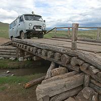 A Smithsonian Museum archaeology team's vehicle crosses a log bridge near Muren, Mongolia.