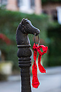 Christmas ribbon on a horse post along historic Meeting Street in Charleston, South Carolina.