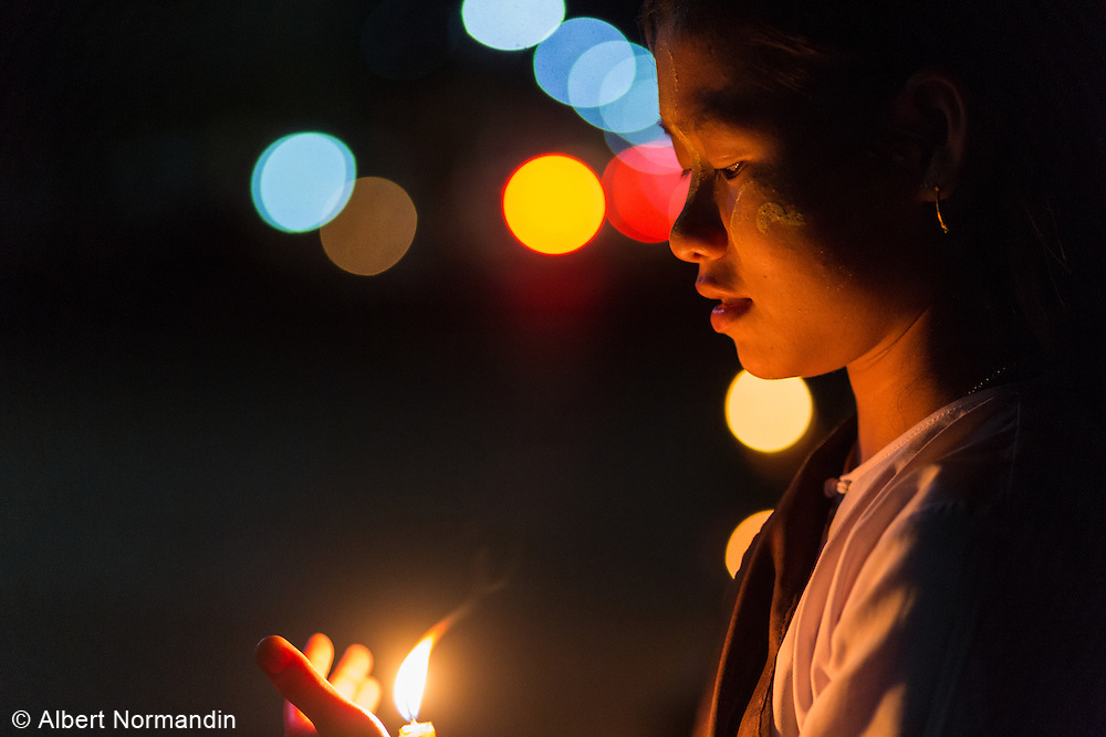 Young student holding candle at night festival, Hpa-an
