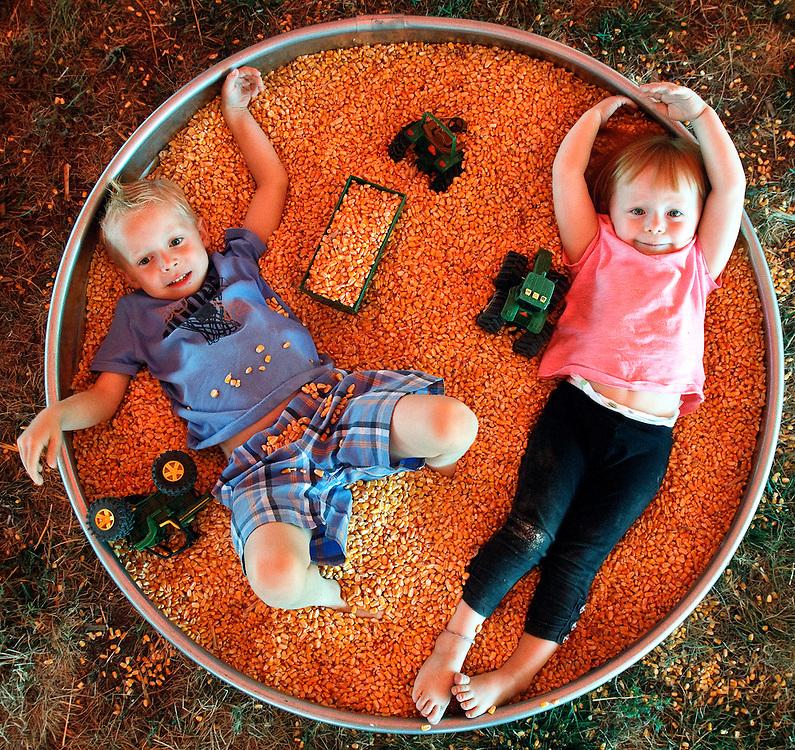 "Raiden Stimple, 5, plays with cousin Kenslie Drake, 2, in a bin of corn Sunday at Nebraska State Fair in Grand Island. ""I'm taking a bath,"" said Stimple.(Independent/Matt Dixon)"