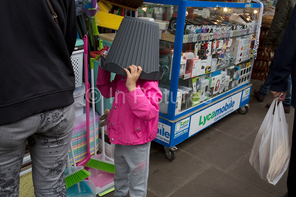 Young girl spontaneously places a bucket on her head in London, England, United Kingdom.