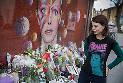 © Licensed to London News Pictures. 10/01/2017. London, UK. Bowie fan Stacey Panton 27, looks at a mural and shrine to David Bowie in Brixton on the first anniversary of his death. David Bowie was born in Brixton, south London. Photo credit: Peter Macdiarmid/LNP