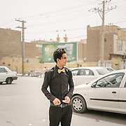 Restaurant waiter waiting for a taxi. In Zahedan city, capital of Sistan Baluchistan province in south east Iran, near the border with Afghanistan. <br /> <br /> Travelling over 4000km by train across Iran. An opportunity to enjoy Persian hospitality, discover Iran's ancient cities and its varied landscapes, from deserts to mountains.