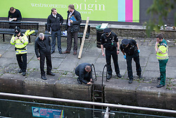 "© Licensed to London News Pictures . 06/10/2013 . Manchester , UK . Police examine the find in the lock . Police pull a body from The Bridgewater Canal in Manchester , adjacent to the City's "" Gay Village "" . The body was spotted yesterday (6th October) afternoon and a cordon was erected as specialist police divers made the recovery . Photo credit : Joel Goodman/LNP"
