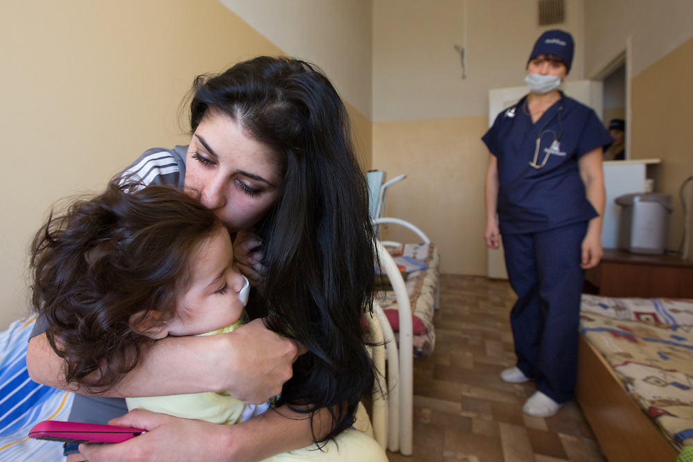 CAPTION: Following a sleepless night and much pacing of the hospital hallway while the operation was in progress, Armena is tremendously relieved to have her little girl back in her arms. LOCATION: Volgograd City Hospital #1, Volgograd, Russia. INDIVIDUAL(S) PHOTOGRAPHED: From left to right: Stella Aharonyan, Armena Vardanan and Lubov Kalganova.