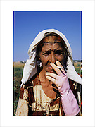 An old woman smokes a cigarette, taking a break from picking tomatoes. Roma Gypsies have worked as poorly paid casual agricultural labourers across Europe. Alexandria, Greece 2006...Roma Gypsies left Rajasthan in India a thousand years ago, in the ninth and tenth centuries. They were pushed west by the Ottoman Muslim Empire as it moved through Persia towards the frontiers of Europe. They entered Europe in the foutrteenth century and were slaves in Romania and Moldavia until the mid 1850s. There are about 15 million Roma gypries in the world, about 12 million who live in Europe. they are Europe's largest ethnic minority. They have rich traditions and culture, their own language. They are renowned for their prowess in music and dance; they are also skilled craftsman, metal roofmakers, silver and goldsmiths. Their traveling and nomadic lifestyle which grew from a necessity to find work, and because they were often moved on from one place to the next, has given them both a liberty but also marks them as different and they are often feared by sedentary peoples, who label and scapegoat them. They are hardy survivors and live in the brunt of racism and prejudice, often marginalised, living in poverty, without proper human rights afforded to them..