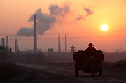 A man drives his tractor past a coking factory at sunrise in Linfen, Shanxi Province, China on Thursday, 03 December, 2009.  Due to the heavy presence of coal mines and related industries, Linfen was named the world's most polluted city from 2004-2007.