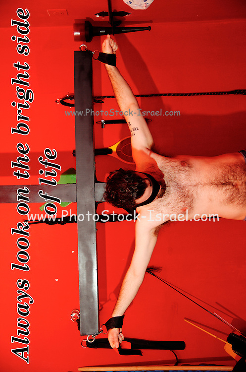 Crucified blindfolded young man in a BDSM dungeon
