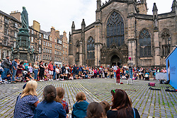 Edinburgh, Scotland, UK. 8th August  2021. On a sunny Sunday afternoon the Royal Mile was busy with visitors looking for the limited street entertainment provided during the much scaled back Edinburgh Fringe Festival this year. Two stages are provided for performers and these proved popular throughout the day. Pic; Crowd watches performer on Parliament Square in front of St Giles Cathedral. . Iain Masterton/Alamy Live news.