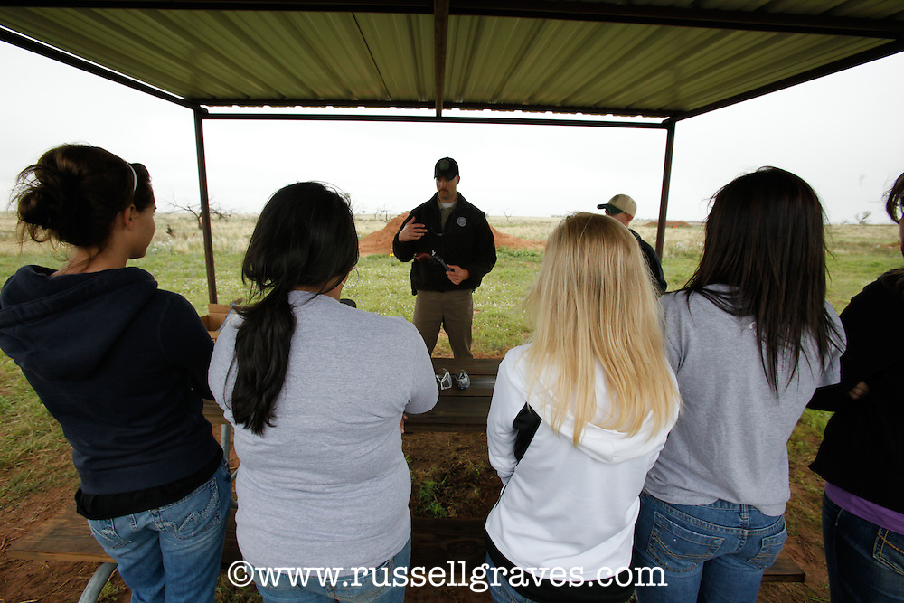 FEMALE STUDENTS LEARNING HOW TO SHOOT A PISTOL
