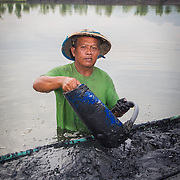 CAPTION: Achmad has been renting his fishpond for 10 years. In this image, he is removing sediment from the bottom of his pond. When it floods, the amount of sediment and waste in his pond increases. LOCATION: Tapak, Semarang, Indonesia. INDIVIDUAL(S) PHOTOGRAPHED: Achmad Siyam.