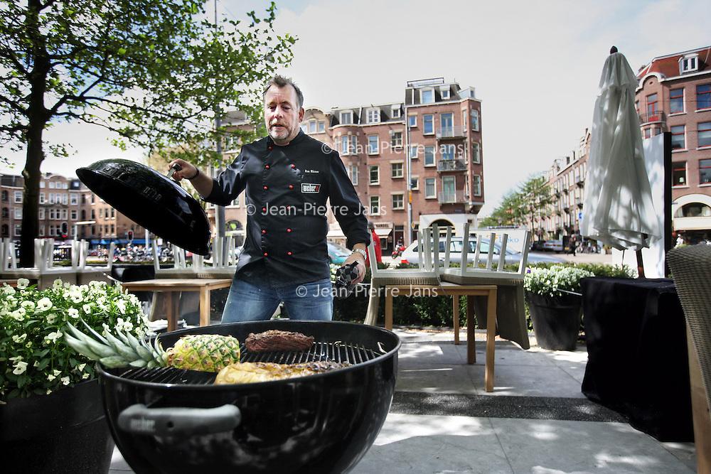 Nederland, Amsterdam , 23 mei 2013.<br /> Topkok Ron Blaauw tijdens barbecuen van long beef en kool buiten op het terras van zijn restaurant aan de Amstelveenseweg.<br /> Ron Blaauw is een  Nederlands chef-kok en televisiepersoonlijkheid.<br /> TV-chef and top chef Ron Blaauw barbequeing beef and cabbage on the terrace of his restaurant