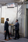 Two businessmen enjoy an informal lunchtime meal outside a City of London bar in Milford Lane, WC2. Standing at a high table, the associates meet and talk business while enjoying a spring lunchtime drink of pints of beer. Above them is a borough of Westminster street sign showing the postcode and street name, a small and very old lane dating back to the medieval era when the capital was spreading westwards from the Roman walled City.