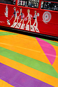 Images of party-girls enjoying the London high-life, appears on the side of a Routemaster Tour Bus as it passes over the multi-coloured markings of a crossing at Piccadilly Circus, on 16th July 2021, in London, England.