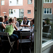 """Stockholm, Sweden, August 15, 2012. Tullstugan Collective. Dinner time on the terrace. """"It's really nice, after a long day, come to set table and get a good, well-cooked dinner served four nights a week."""" says the Tullstugan's website. <br /> On the center, Mr Dick Urban Vestrbro, Chairman of the Swedish Co-housing association Kollektivhus NU.<br /> People living in the collective are having a meeting after dinner."""