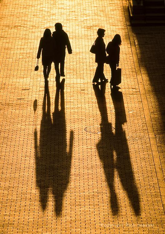 Pedestrians cast long shadows near sunset, Odaiba district, Tokyo, Japan
