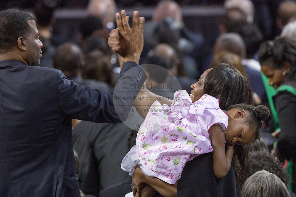 Mourners high five during a standing ovation for U.S. President Barack Obama at the funeral service for slain State Senator Clementa Pinckney at the TD Arena June 24, 2015 in Charleston, South Carolina. Pinckney is one of the nine people killed in last weeks Charleston church massacre.