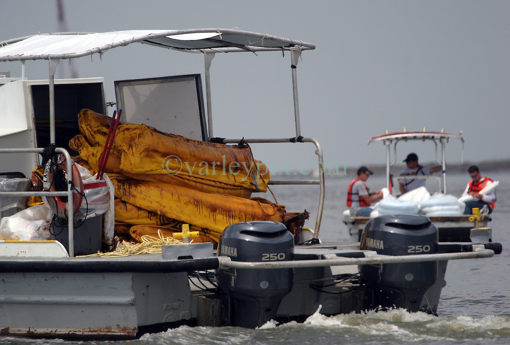 26 May 2010. Barataria Bay to Grand Isle, Jefferson/Lafourche Parish, Louisiana. <br /> Oil washed up on boom is taken out on a shrimp boat in Grand Isle. The economic impact is devastating with shrimp boats tied up, vacation rentals and charter boat fishing trips are cancelled. Oil from the Deepwater Horizon catastrophe is evading booms laid out to stop it thanks in part to the dispersants which means the oil travels at every depth of the Gulf and washes ashore wherever the current carries it. <br /> Photo credit; Charlie Varley<br /> www.varleypix.com