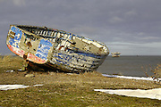 A derelict fishing boat sits alone on the beach at Sizewell in suffolk