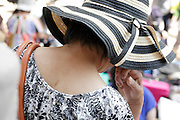 close up of woman with shoulder bag and hat