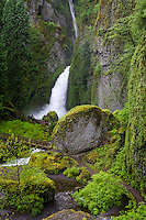 Wachlella Falls in the Pacific Northwest of Oregon rushes down to the canyon floor and under a footbridge during a Spring rainstorm.