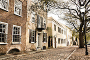 Traditional stuccoed homes and cobblestone on Gillion Street in historic Charleston, SC.